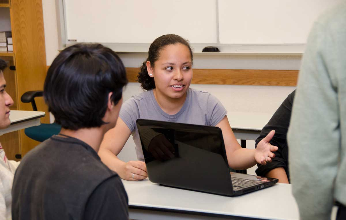 young woman explaining infront of a laptop