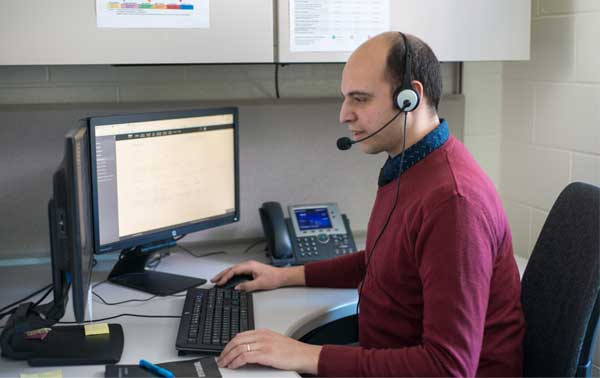 man wearing a headset working at computer