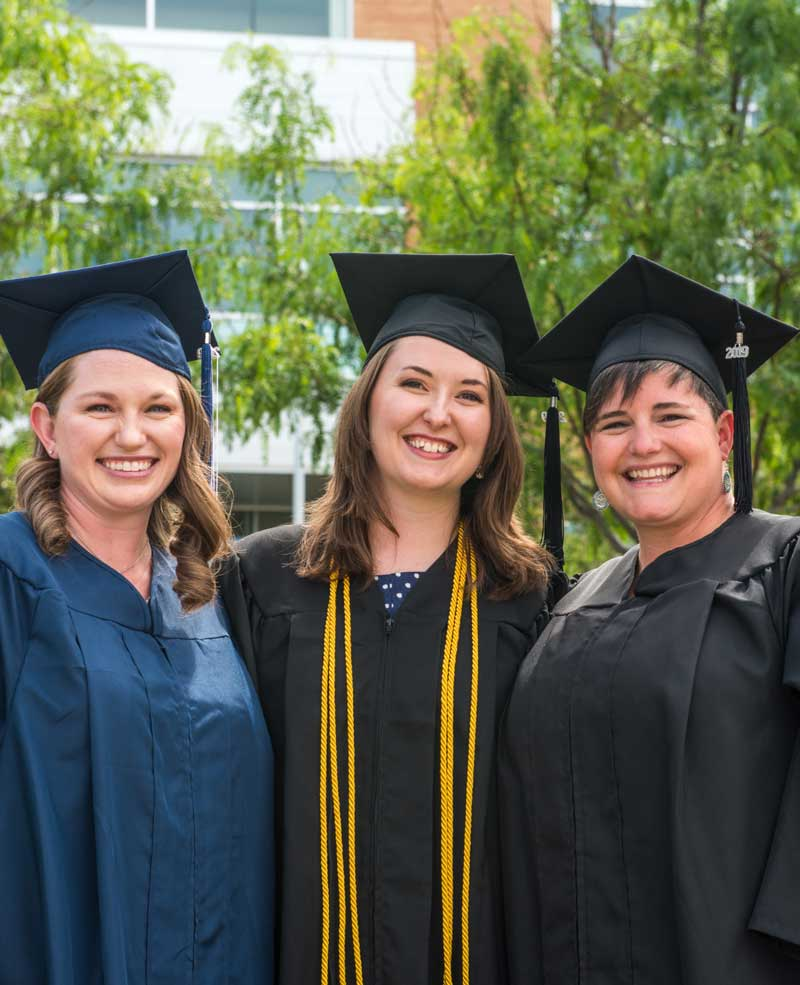three women wearing college graduation cap and gown outside